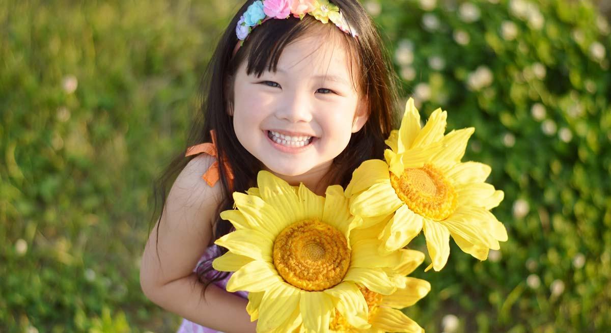 笑顔でひまわりを抱える小さい女の子