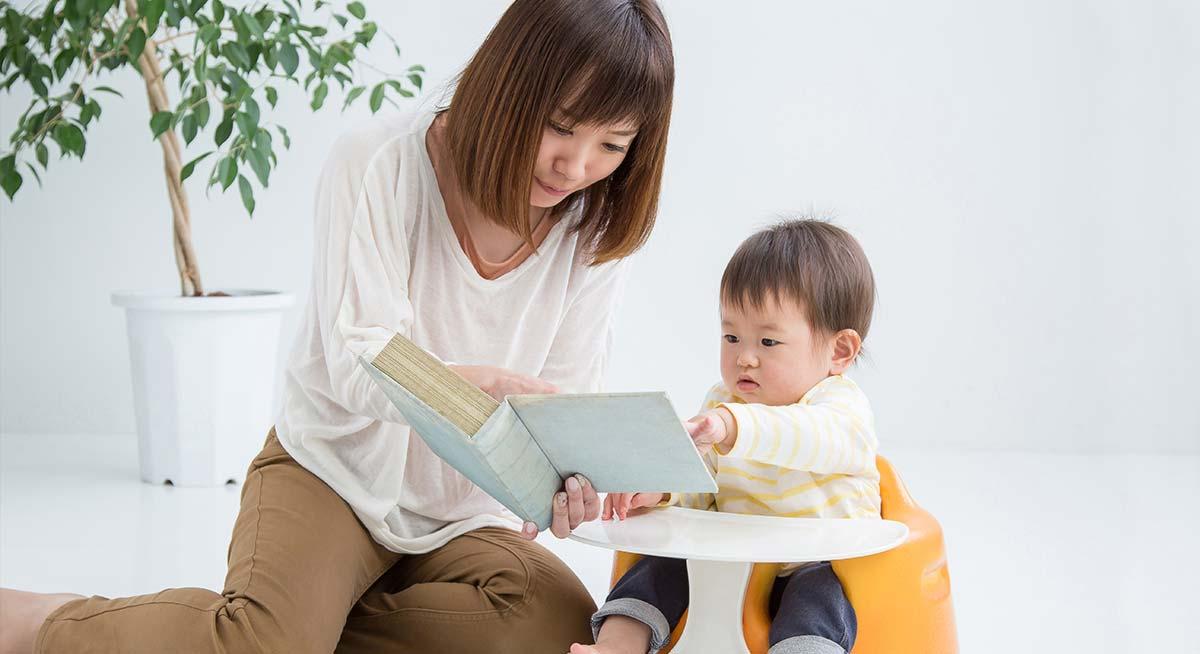 赤ちゃんに絵本を読んであげる女性